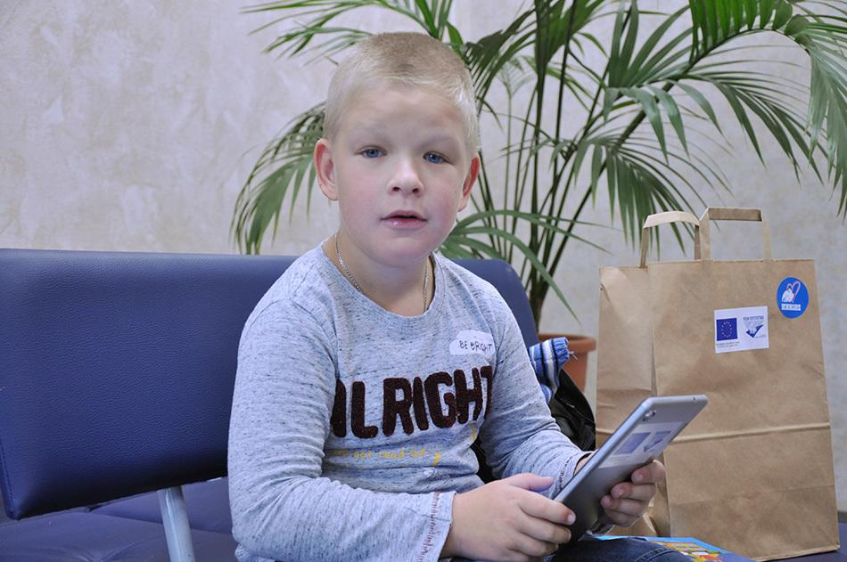 ребенок держит в руках планшет от